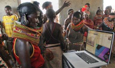 Turkana women examine photos of a festival rehearsal on a laptop in Loiyangaleni, Kenya.